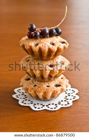 Three muffins and black currants on wooden background - stock photo