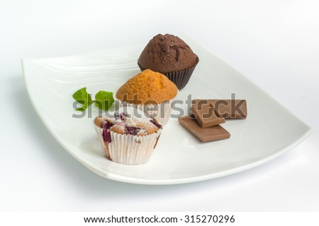 Three muffins with different flavors on a big white plate - stock photo