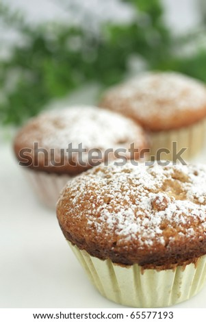 Three muffins with sugar powder on top