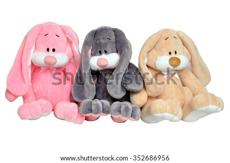 Three multi-colored plush rabbit isolated on white background. Soft toy bunnies sitting in a row. - stock photo