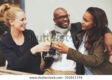 Three multi ethnic friends having a good time on a cafe - stock photo