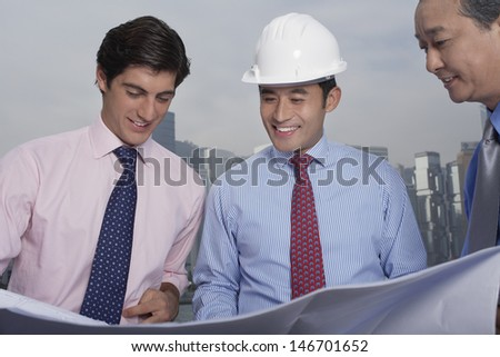 Three multiethnic male architect looking at blueprint with buildings in background - stock photo