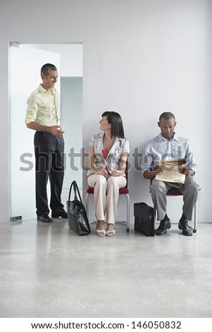 Three multiethnic people waiting in corridor at the office - stock photo