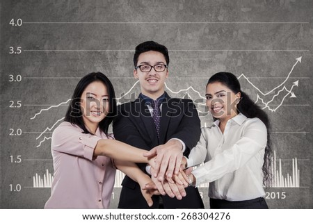 Three multiracial businesspeople smiling at the camera while joining their hands with financial graph background - stock photo