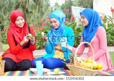 Three muslim girl picnic at park - stock photo