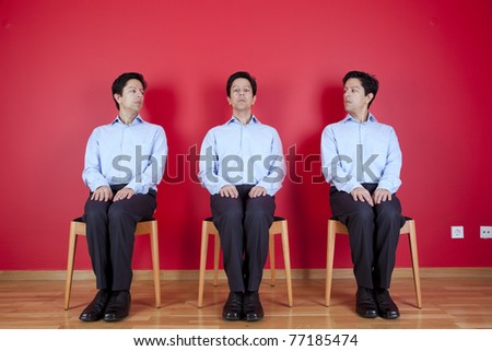 three nerd businessman with a suspicion look to each other, next to a red wall - stock photo