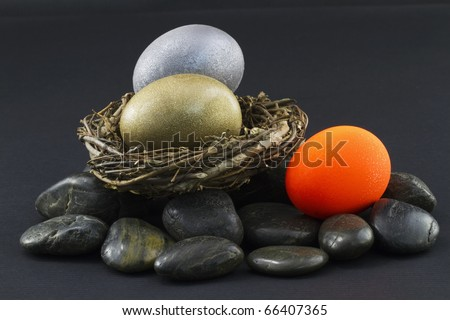 Three nest eggs with silver and gold doing well in nest and red nest egg on the rocks signifying an at risk sector - stock photo