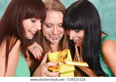 three nice girls in green dresses on a green with a gift - stock photo