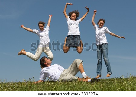 Three nice girls jump on a green grass on a background of the blue sky, and young the man lays before them and looks at them from below