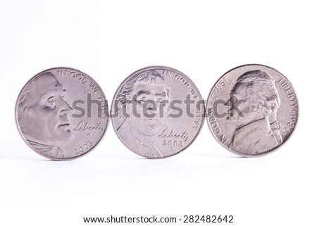 Three nickel faces standing on the edge with white background. - stock photo