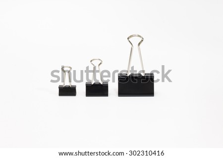 three office paper clips of different sizes on a white background - stock photo