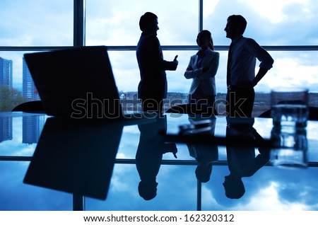 Three office workers interacting by the window with their workplace in front - stock photo
