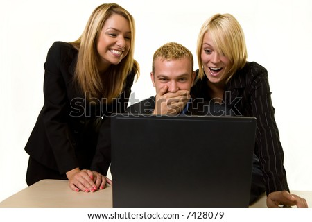 Three office workers one man and two women all looking at a computer screen with laughing and shocked expressions