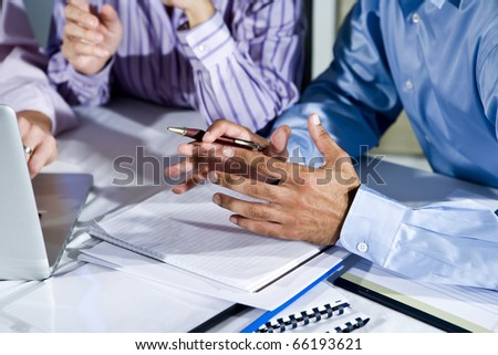Three office workers working together on project, gesturing, focus on hand in middle - stock photo