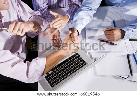 Three office workers working together on project, shaking hands and clapping.  Finished project or solved a problem.