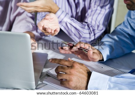 Three office workers working together on project using laptop, gesturing, focus on pen
