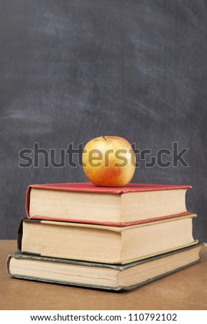 Three old books sit on a desk with an apple on top in front of a blackboard.