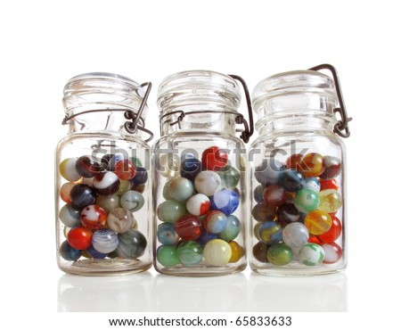 Three old jars contain a collection of colorful antique marbles - stock photo