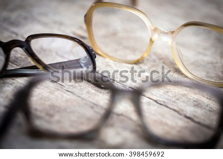 three old nerdy hornrims or eye glasses on wooden table