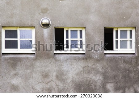 Three old windows on old dirty wall - stock photo