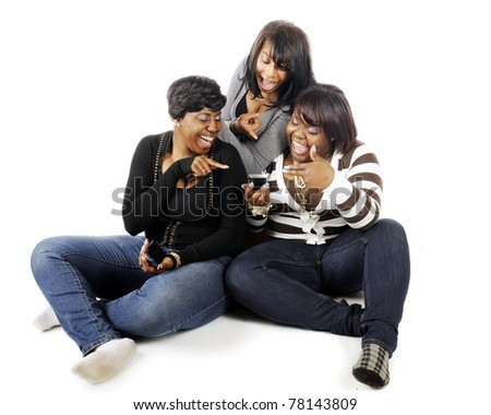 Three older teen friends laughing over an cell phone message.  Isolated on white.