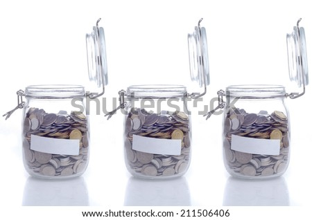 Three open glass jar with coin and empty space for text  - stock photo