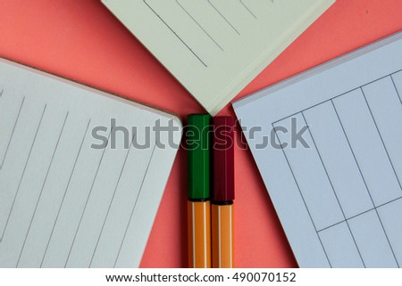 Three open notebooks and two pens on pink background