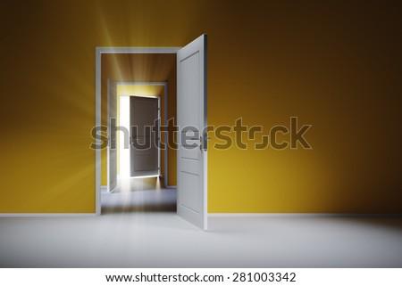 Three open white doors on the blue wall. Rays of light shine through the open door. - stock photo