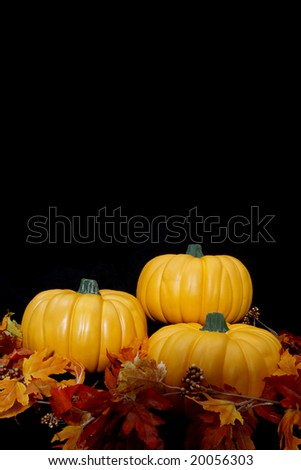 Three orange autumn pumpkins arranged on a black background with some leaves.