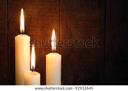 Three ordinary lighting candles against old wooden texture with free space for your text - stock photo