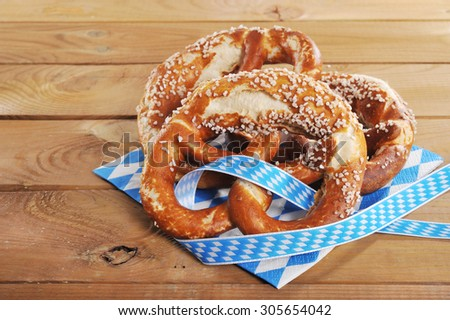 three original bavarian salted soft pretzels from Germany in front of wooden board - stock photo