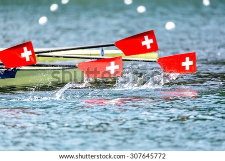 Three paddles with swiss coat of arms logo coming up out of the water. - stock photo