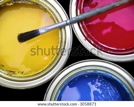 Three paint cans with one brush on top