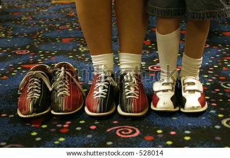 Three pair of bowling shoes. Two being worn, one empty. - stock photo