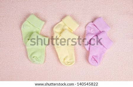 Three pairs of baby socks on a pink terry towel - stock photo