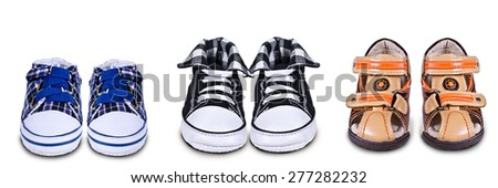 Three pairs of childrens shoes on an isolated background. - stock photo