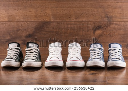 three pairs of cool youth white gym shoes with red  stripes  on brown wooden floor  standing in line with copy place  - stock photo