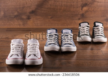 three pairs of cool youth white gym shoes with red  stripes  on brown wooden floor  standing in line with perspective  - stock photo