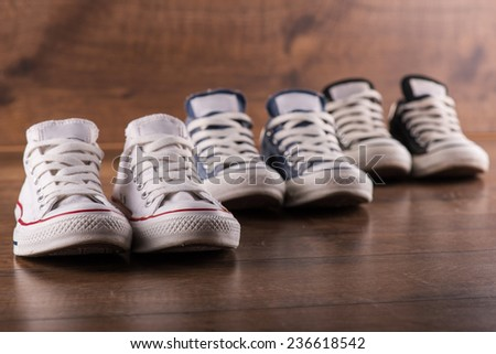 three pairs of cool youth white gym shoes with red  stripes  on brown wooden floor  standing in line with perspective and  selective focus  - stock photo