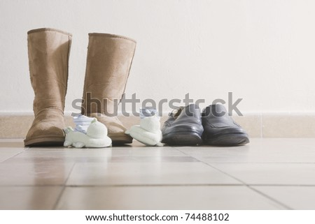 Three pairs of shoes by the front door of a home. - stock photo