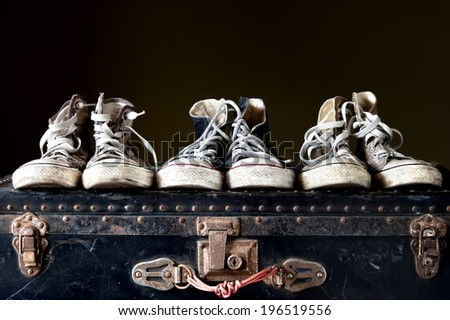 Three pairs of sneakers on vintage suitcase - stock photo