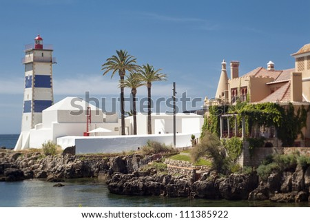 Three palm-trees near Santa Marta lighthouse in Cascais, Portugal. Photo is made with the TS-lens. - stock photo