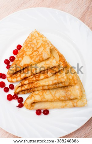 Three pancake folded triangle with red berries on a white plate
