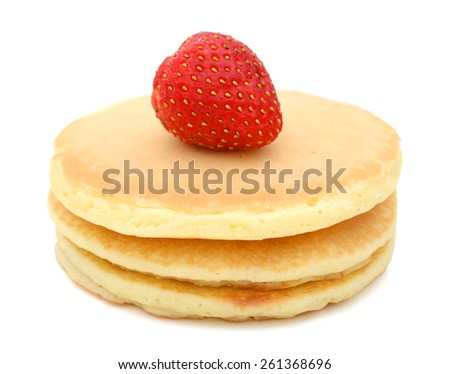 three pancakes and one strawberry isolated on white