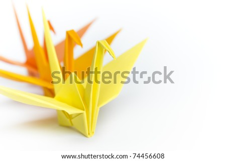 Three paper birds lining up on a white background, shallow depth of field - stock photo
