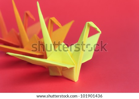 Three paper birds on a red background, shallow depth of field - stock photo