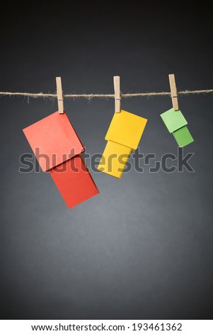Three paper houses in different colors hanging on a rope line with clothespins. - stock photo