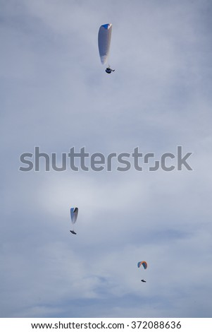 three paragliders flying in cloudy white and blue sky - stock photo