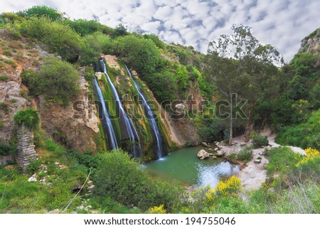 Three parallel streams of water running down the steep slope and fall in oval pool. Unusual three-jet waterfall in northern Israel - stock photo