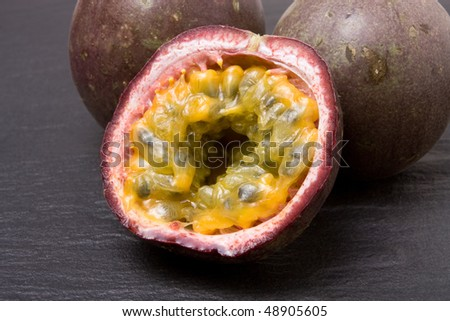 Three Passion Fruit one sliced on dark slate background. - stock photo